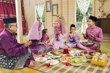 Muslim family saying prayers before meal Stock Photo
