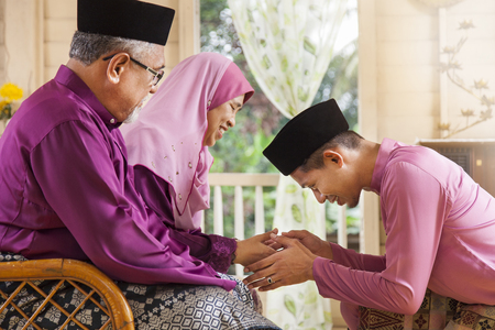 Traditional act of respect in Muslim family on Eid al-Fitr Banque d'images
