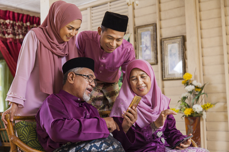 Muslim family looking at a mobile phone Imagens