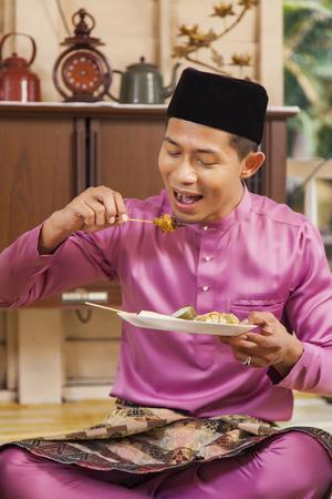 Muslim man eating satay during Eid al-Fitr