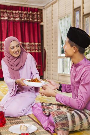 穆斯林妇女为一碗鸡rendang服务给一个人