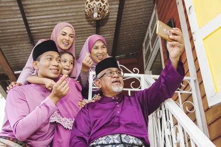 Muslim family taking self-photograph outside the house
