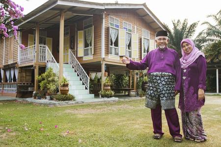 站立在他们的房子外面的穆斯林夫妇