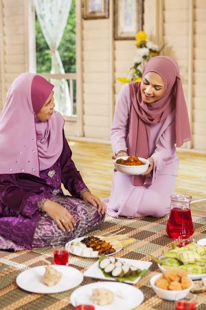 开斋节期间,一名妇女在为父母上菜