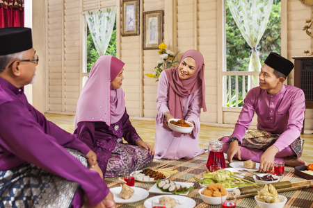 Woman serving food to her parents during Eid al-Fitr