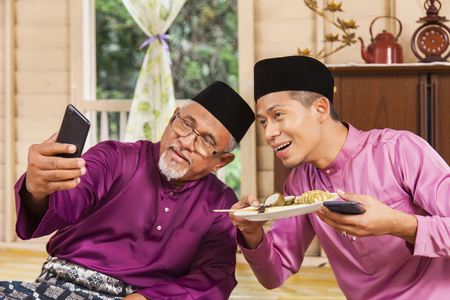 Senior Malay man taking self-photograph with his son Stock Photo - 120409427