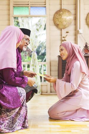 Senior muslim woman receiving green envelope from her daughter during Eid al-Fitr