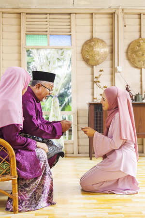 Senior muslim man receiving green envelope from his daughter during Eid al-Fitr