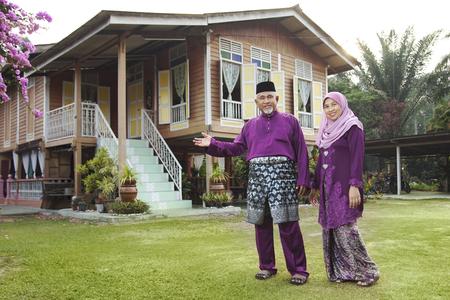 Couple musulman debout devant leur maison