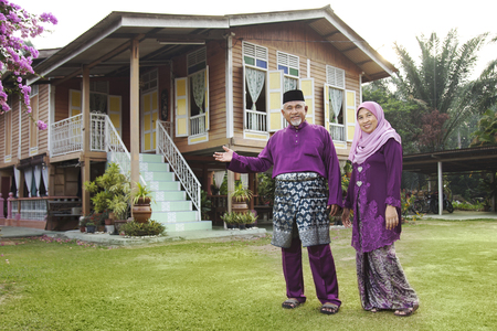 Muslim couple standing outside their house