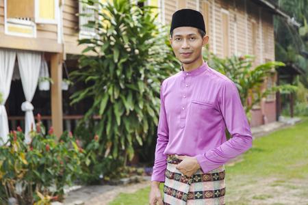 站立在他的房子外面的穆斯林人