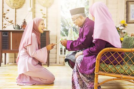 Älterer muslimischer Mann, der während Eid al-Fitr . einen grünen Umschlag von seiner Tochter erhält