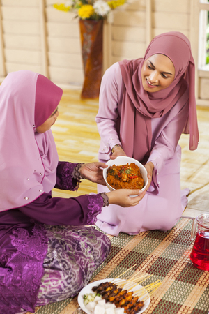 Woman serving food to her parent during Eid al-Fitr