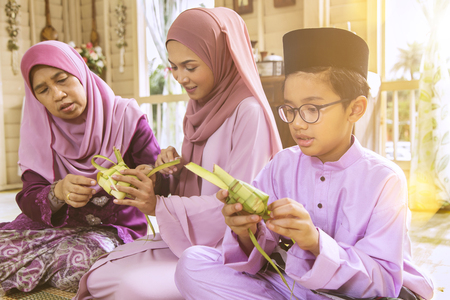 Muslim family weaving ketupat
