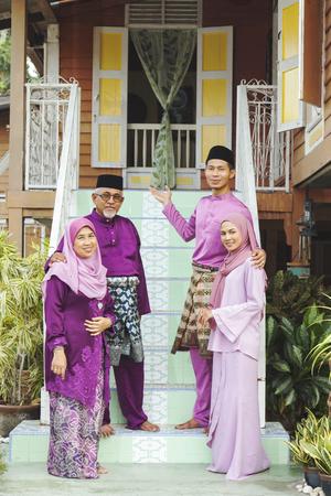 站立在他们的房子外的穆斯林家庭