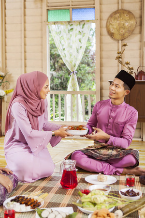 Muslim woman serving a bowl of chicken rendang to a man