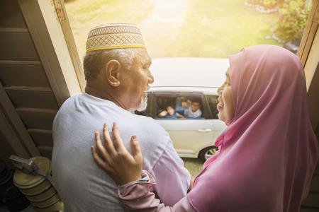 Grands-parents saluant leurs petits-enfants dans la voiture Banque d'images