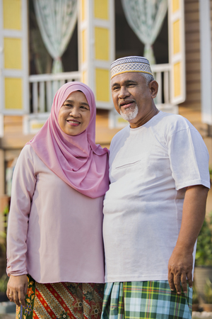Senior couple in front of wooden house 版權商用圖片