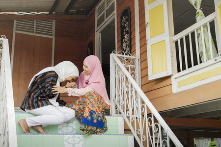 妇女招呼她的母亲用握手
