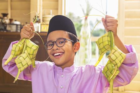 Muslim boy holding ketupats