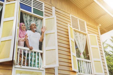 一对老年夫妇从窗户向我挥手