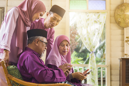 Muslim family looking at a mobile phone