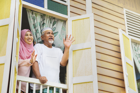 Senior couple waving from house window