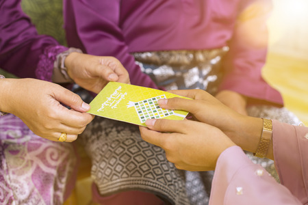 Muslim woman receiving green envelope from senior woman during Eid al-Fitr Stock Photo