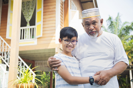 Boy with his grandfather in front of wooden house