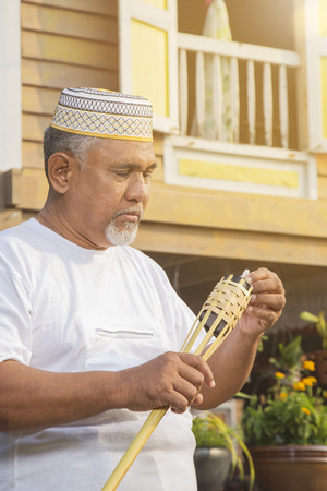 Senior man setting up bamboo torch lamp
