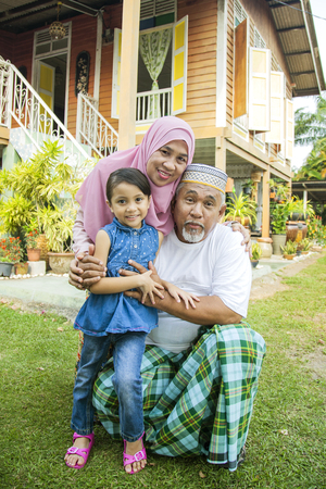 Girl with her grandparents in front of wooden house