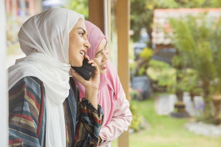 Mother and daughter listening to a call on mobile phone