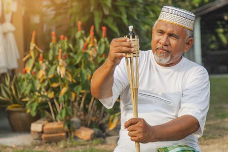 Hombre Senior configurando lámpara de antorcha de bambú