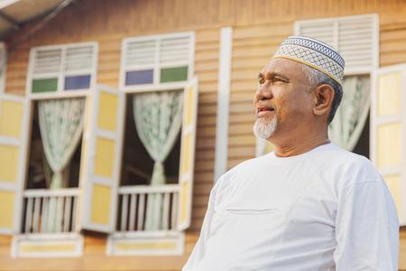Senior man standing in front of wooden house