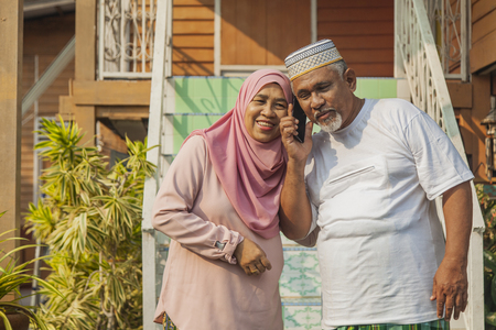 Senior couple listening to a call on mobile phone Stock Photo