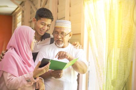 Famiglia con un biglietto di auguri Eid e uno smartphone