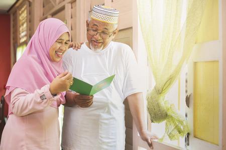 Senior couple reading an Eid greeting card