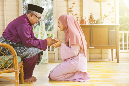 Traditional act of respect in Muslim family on Eid al-Fitr 版權商用圖片