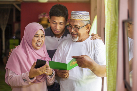 Parents and son with an Eid greeting card looking at smartphone