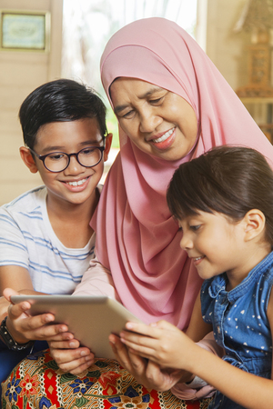 Grandmother and grandchildren using digital tablet
