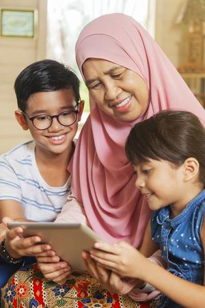 Großmutter und Enkelkinder mit digitalem Tablet