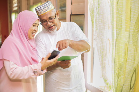 Senior couple with an Eid greeting card looking at smartphone