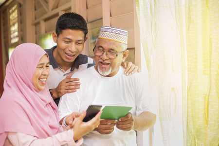 Family with an Eid greeting card and smartphone 版權商用圖片 - 121404380