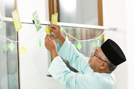 Muslim man decorating home for Eid al-Fitr