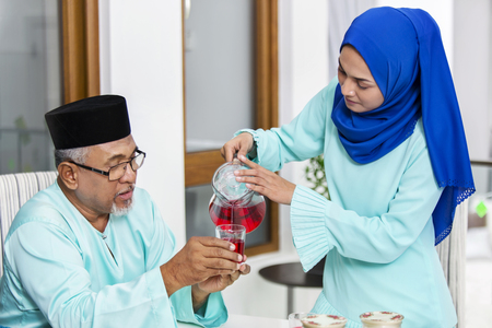 Muslim woman serving beverage to her parent