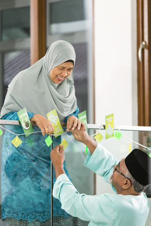 Muslim couple decorating their home for Eid al-Fitr