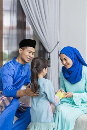 Muslim girl receiving green envelope from parents during Eid al-Fitr