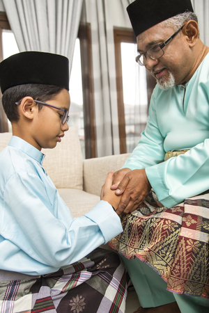 Traditional act of respect in Muslim family on Eid al-Fitr Stockfoto