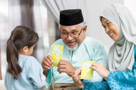 Senior Muslim couple showing green envelopes to their granddaughter
