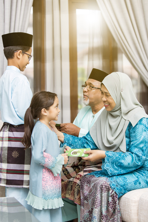 Muslim kids receiving green envelope from grandparents during Eid al-Fitr Stock Photo